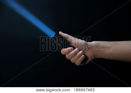 Black Flashlight A Beam Of Light Directed At The Top In Male's Hand Isolated From Right Side Of The