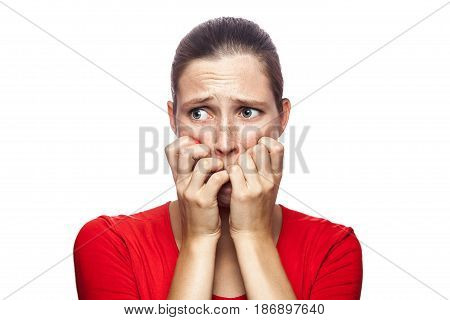 Portrait of worried scared woman in red t-shirt with freckles. looking at camera studio shot. isolated on white background.
