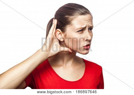 Portrait of woman in red t-shirt with freckles trying to listening. studio shot. isolated on white background.