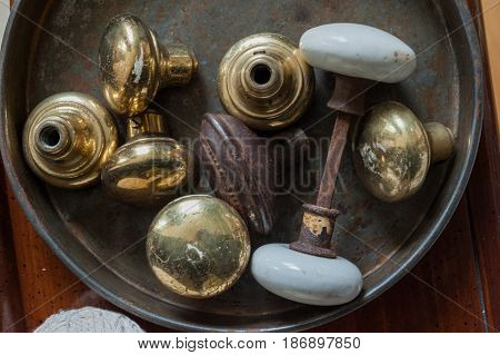 Tin can with rusty and aged door knobs