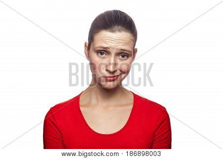 Portrait of sad unhappy woman in red t-shirt with freckles. studio shot. isolated on white background.
