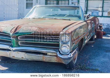 GOSHEN VIRGINIA- APRIL 8 2017: Old car rusting away in front of an abandoned repair shop.