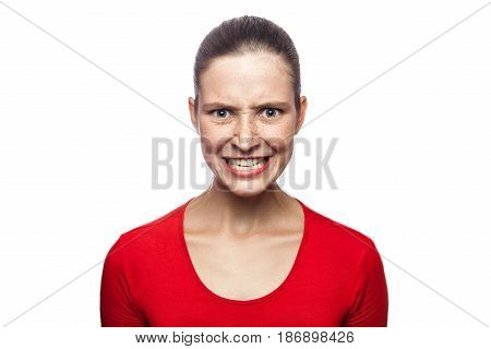 Portrait of worried angry woman in red t-shirt with freckles. looking at camera and screaming studio shot. isolated on white background.
