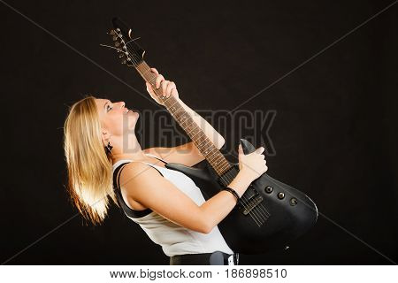 Music singing concept. Blonde musically talented woman holding electric guitar on black background
