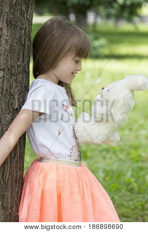 Little Girl Standing Beside A Tree Holding Her Favorite Stuffed Toy