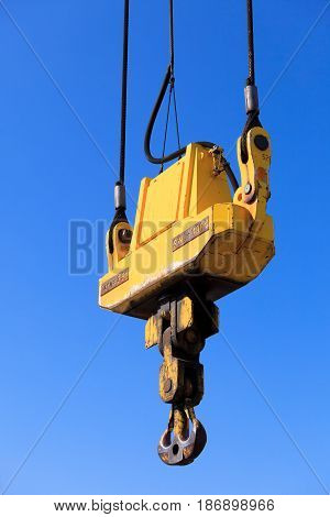 Business and commerce. Closeup crane hook at port area and blue sky cargo container yard. Industrial scene