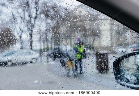 Silhouette of postman postal worker on bike crossing street on a snowy day - senn by the driver point ov view personal perspective through wet windshield window