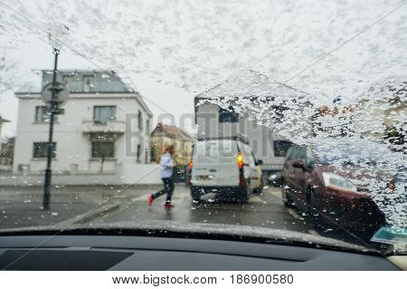 Silhouette of woman crossing street on a snowy day - senn by the driver point ov view personal perspective through wet windshield window