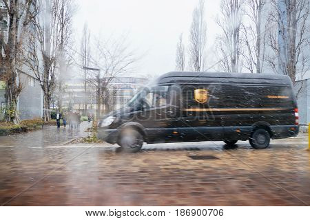PARIS FRANCE - JAN 4 2017: UPS United Parcel Service van delivery brown UPS van driving fast on a snowy rainy day to deliver on time the parcel