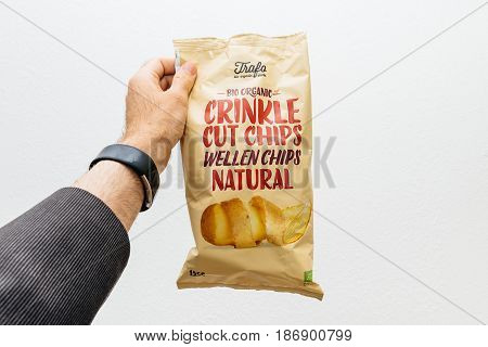 PARIS FRANCE - MAY 10 2017: Man hand holding against backgroind a package of Bio Organic Trafa Crinkle Cut Chips