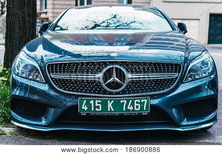 PARIS FRANCE - APR 2 2017: Front view of luxury Mercedes-benz car in majestic blue lava color with green diplomatic plates parked on a street