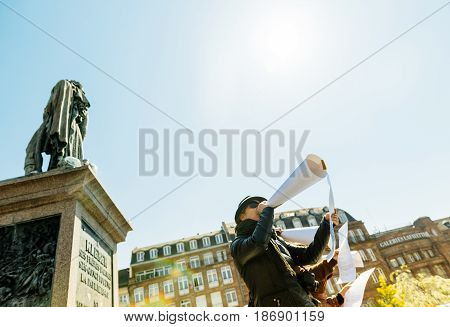 STRASBOURG FRANCE - APR 20 2016: Group of people with improvised megaphones made from paper talking loud to the crowd at protest with statue of General Kelber in central Strasbourg Alsace