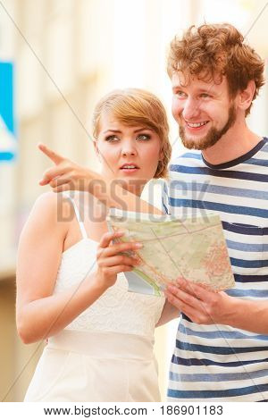 Tourist Couple In City Looking Up Directions On Map