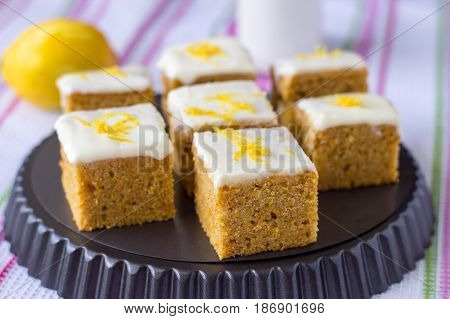 Pieces of homemade carrot cake with orange lemon zest and icing cream. Selective focus