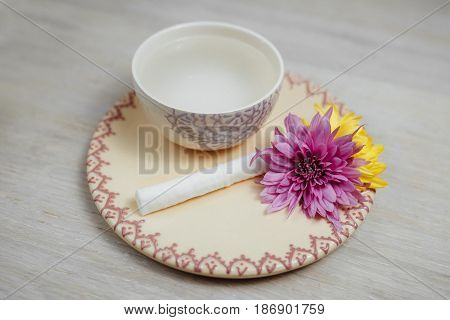 A cup of water and two flowers on a saucer