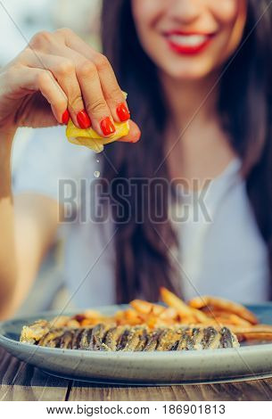 Woman Squeeze Lemon On Portion Of Fish In A Restaurant
