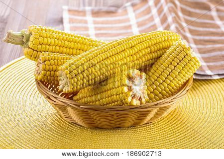 Corn cobs close-up in wicker basket background of yellow wicker mat and boards