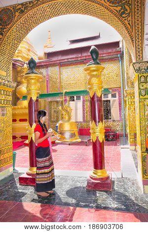 MANDALAY,MYANMAR - MARC 7, 2017: Myanmar woman ringing the bell  Su Taung Pyi Pagoda on top of Mandalay Hill on March 7, 2017, in Mandalay, Myanmar (Burma)