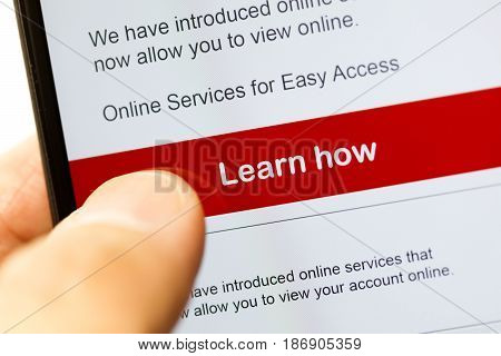 smartphone touch screen with red button learn how. business e-commerce concept.