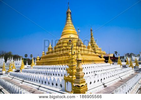 Golden Sandamuni Pagoda with row of white pagodas. Amazing architecture of Buddhist Temples at Mandalay. Myanmar (Burma)