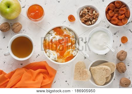 Cottage cheese with apricot jam sour cream yogurt dried apricot apple walnut and cup tea with biscuits for healthy breakfast