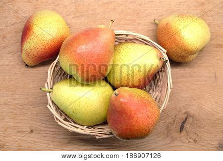 Red and yellow pears lays in small wicker straw basket on brown wooden table top view closeup