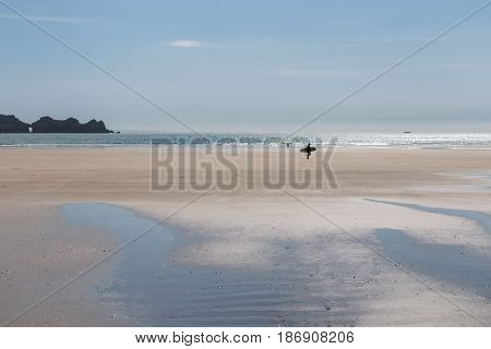 Surfer walking over wide sandy summer beach with sea and rocky coastline in background. People silhouetted by bright sunshine reflected on the water surface.