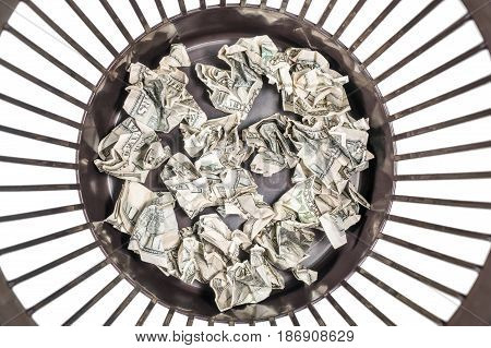 Crumpled hundred-dollar banknotes of money at the bottom of the trash can, close-up