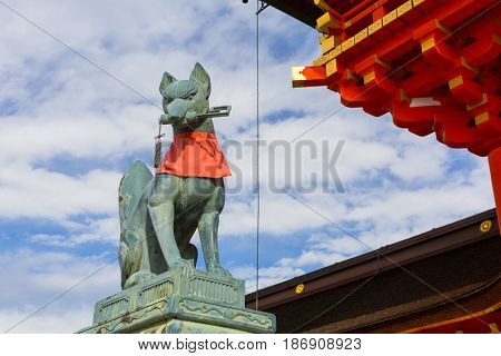 KYOTO, JAPAN - NOVEMBER 10, 2016 : Stone fox on guard at Fushimi Inari Shrine torii gate in Kyoto, Japan. Torii is a traditional Japanese gate commonly found in a shrine.