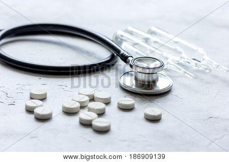stethoscope, pills, vials in medical room on white desk background