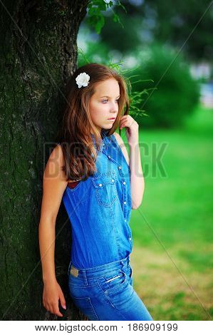 Portrait of elegant modest well-groomed girl in the blue denim suit leaning against a great tree in a summer Park on a blurred background of green bushes close-up