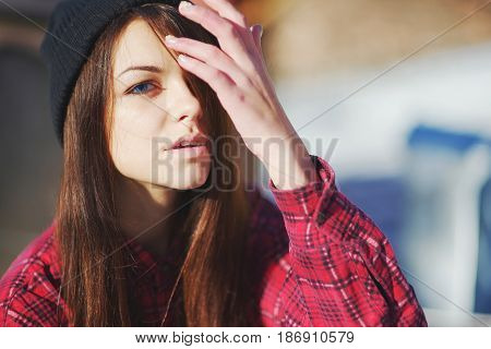 Portrait of young pretty long-haired girl brunettes with blue eyes in the hat straightens the arm hair on a bright Sunny day the background will look blurry on the street close-up