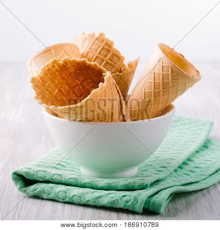 Cones for ice cream in a white bowl on the table