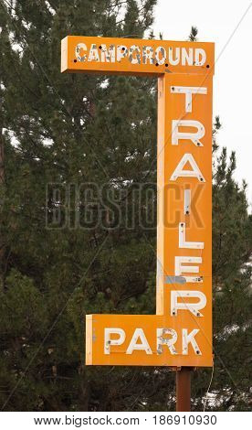 An orange sign advertising camping and camper parking needs repair