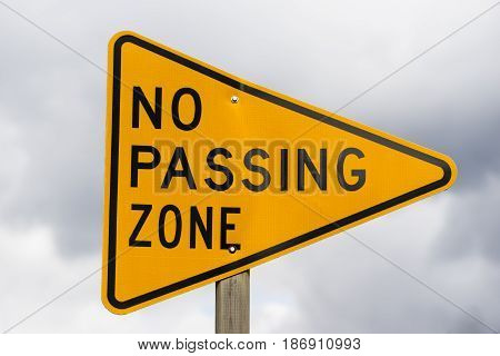 A reflective sign bolted to a post says no passing zone