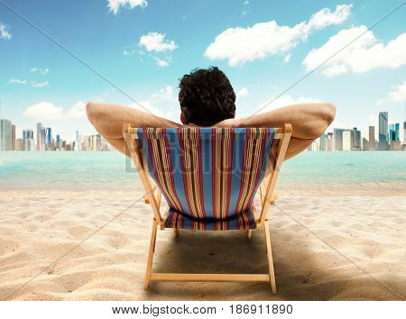 Relaxed businessman on the deck chair at the sea looks at the city