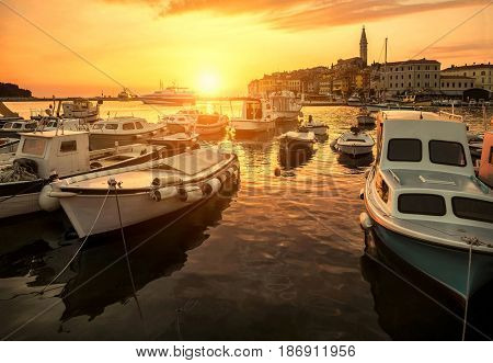 The white boats stay near the pier in port on the sealine under sunlight at summer day. Travel place Rovinj  in Croatia.