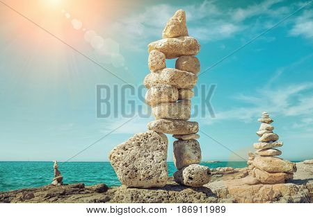 Composition of stones on the seacost under blue sku with clouds on sunny day.
