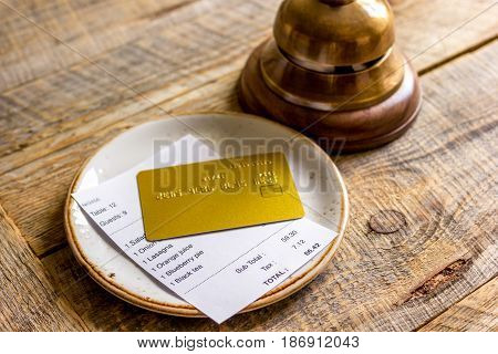 plate and receipt bill for payment by credit card on wooden table background