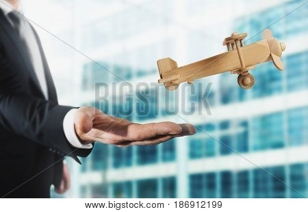 Businessman holding a small wooden aircraft. Startup working enterprise concept