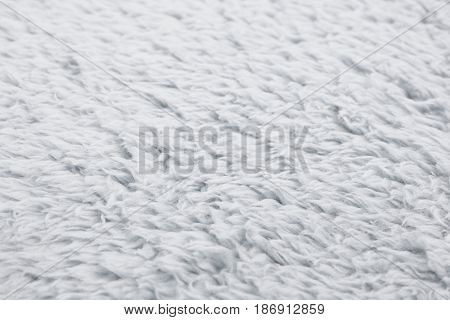 Close-up fragment of a gray colored artificial fur texture as a backdrop composition with a shallow depth of field