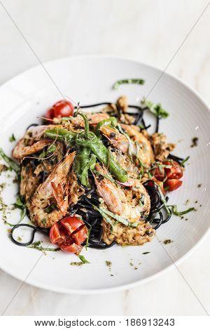 gourmet food grilled prawn and vegetables on black squid ink pasta meal