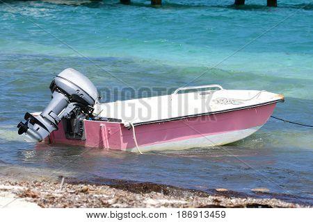 Small outboard skiff on Caribbean beach, BVI