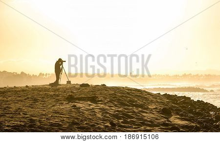 Silouette of male photographer at California beach during sunrise