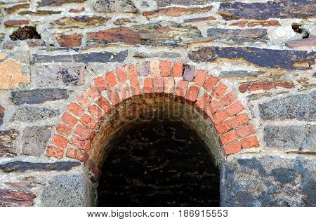 Brick Arch Around The Entrance To An Old Derelict Historical Stone Built Building