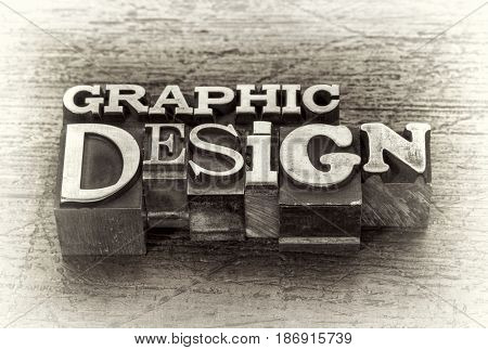 graphic design word abstract in mixed vintage metal type printing blocks over grunge wood, black and white image