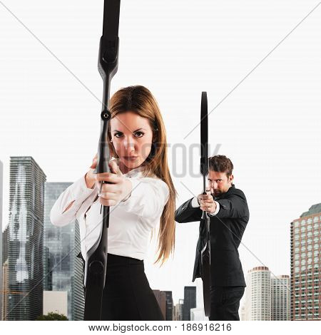 Determined Businesspeople with bow and arrow aiming a target