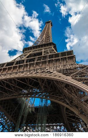 Upwards view from below the Eiffel Tower Tour Eiffel blue sky clouds