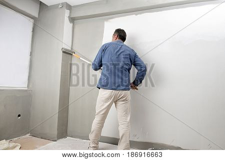 Real professional painter painting house interior with paint roller.