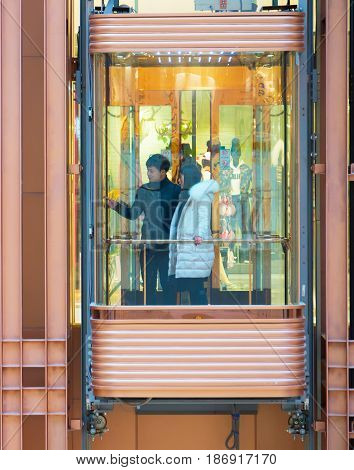 Couple In Shopping Mall Lift